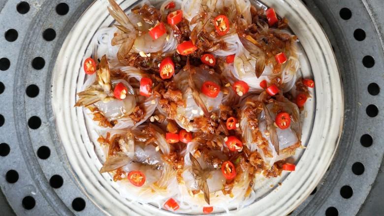 蒜蓉蒸大虾,再摆上小米辣圈。上锅隔水蒸,开锅后8分钟即可。时间一到,掀开锅盖,浓郁的蒜蓉香气裹着热浪扑面而来。