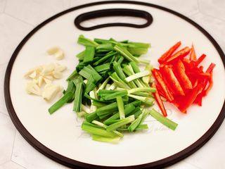 韭菜炒豆芽,紅椒去筋洗凈用刀切成條,韭菜切掉,大蒜切薄片。