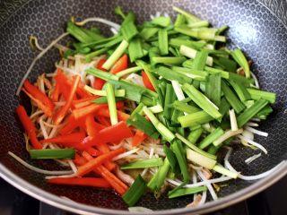 韭菜炒豆芽,加入紅椒條和韭菜段。