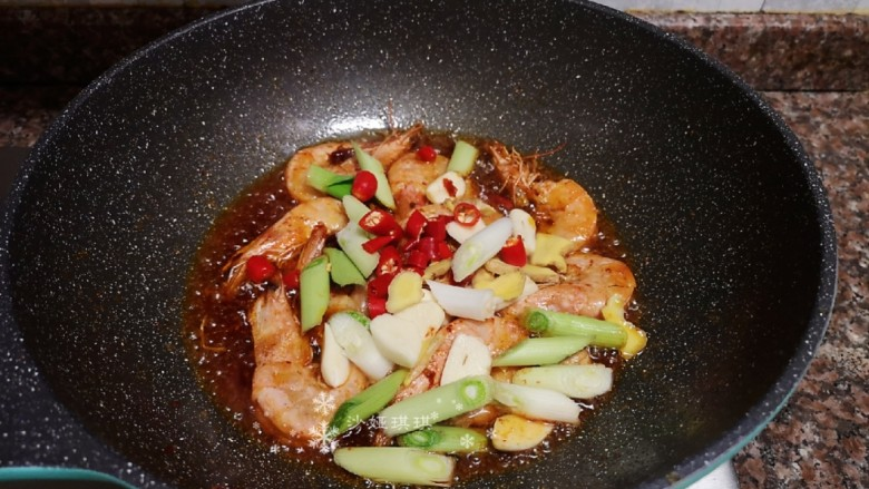 麻辣干锅虾,放入生姜、大蒜、蒜苗头和小米辣翻炒片刻。