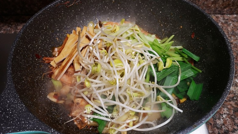 麻辣干锅虾,放入豆芽、豆腐干和蒜苗叶翻炒均匀。