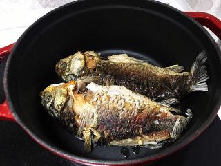 奶白鲫鱼豆腐汤,鱼煎好后移到预热好的铸铁锅或者砂锅里;