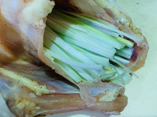 盐焗手撕鸡,将大葱丝和姜丝塞入鸡肚子;