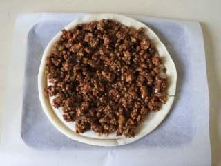 黑椒牛肉披萨,烤盘里铺上硅油纸,把饼底放上面。铺一层牛肉酱,