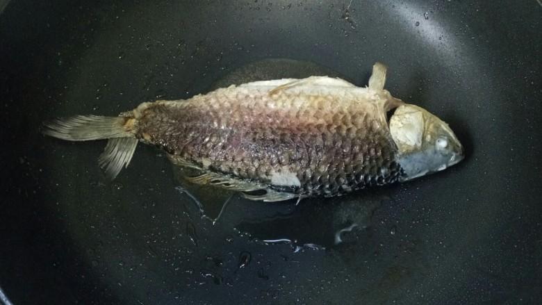 酱焖鲫鱼,鱼腌好用厨房纸巾吸干水份,锅中倒入适量油烧热,放入鱼煎至两面金黄,盛出备用