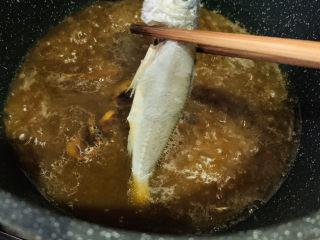 红烧小黄鱼,汤汁煮沸时,用筷子夹入小黄鱼;