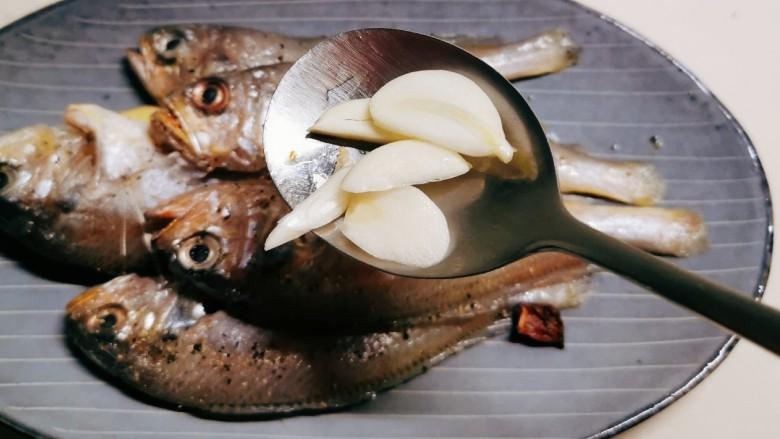 清蒸小黄鱼,放入蒜片