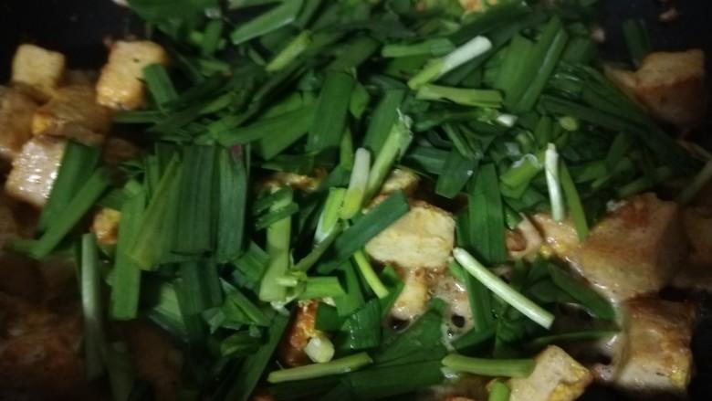 韭菜炒豆腐,倒入韭菜。