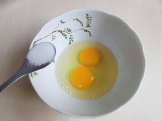 茼蒿炒鸡蛋,鸡蛋打入碗里,加入食盐,用筷子打匀。