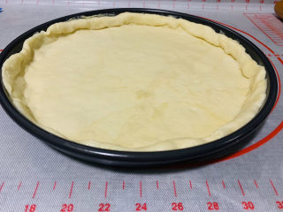 芒果披萨,然后放入披萨盘,边缘挤出圆圈;