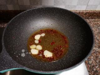蒜苔炒牛肉,放入大蒜片翻炒出香味。