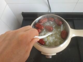 苹果银耳红枣汤,用勺子搅拌至冰糖融化