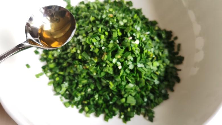 韭菜猪肉馅水饺,切好的韭菜放入盆里,加入刚才烧好晾凉的花椒油,让韭菜都均匀的沾上油,这样可避免韭菜接触盐分而出水。 敲重点❗️韭菜封油。 ‼️花椒油一定要凉透才可以加入韭菜中。