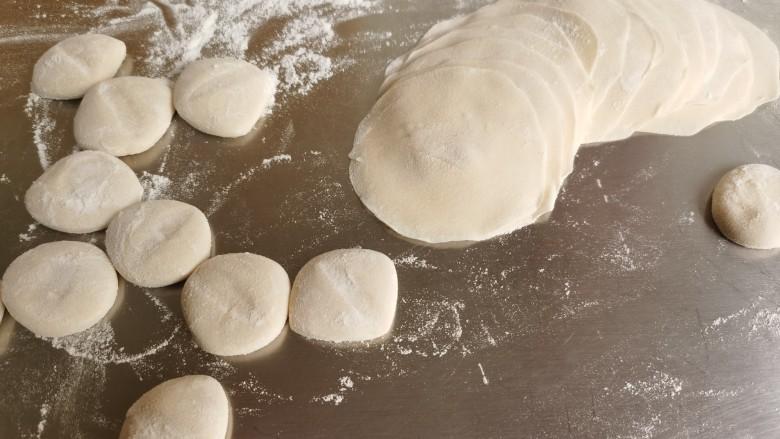 韭菜猪肉馅水饺,将面剂子按扁,用擀面杖擀成四周薄中间厚的圆形饺子皮。