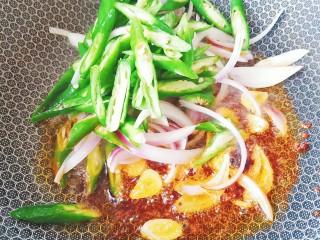蒜苔炒牛蹄筋,加入洋葱丝,青椒丝翻炒均匀