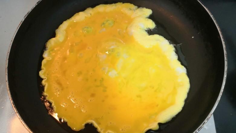 莴笋炒鸡蛋,倒入鸡蛋液,烧至鸡蛋液底部凝固