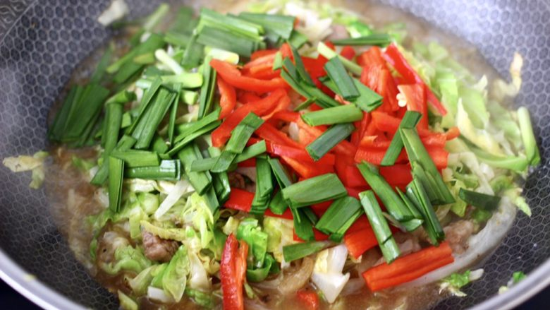 爆炒卷心菜,加入红椒丝和韭菜段。