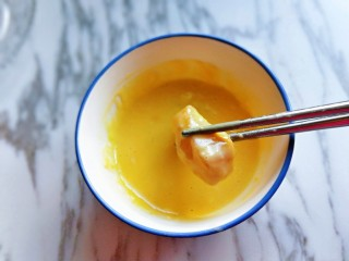 糖醋龍利魚,之后用筷子夾起腌制好的龍利魚,放入蛋糊中,使龍利魚掛滿面糊。