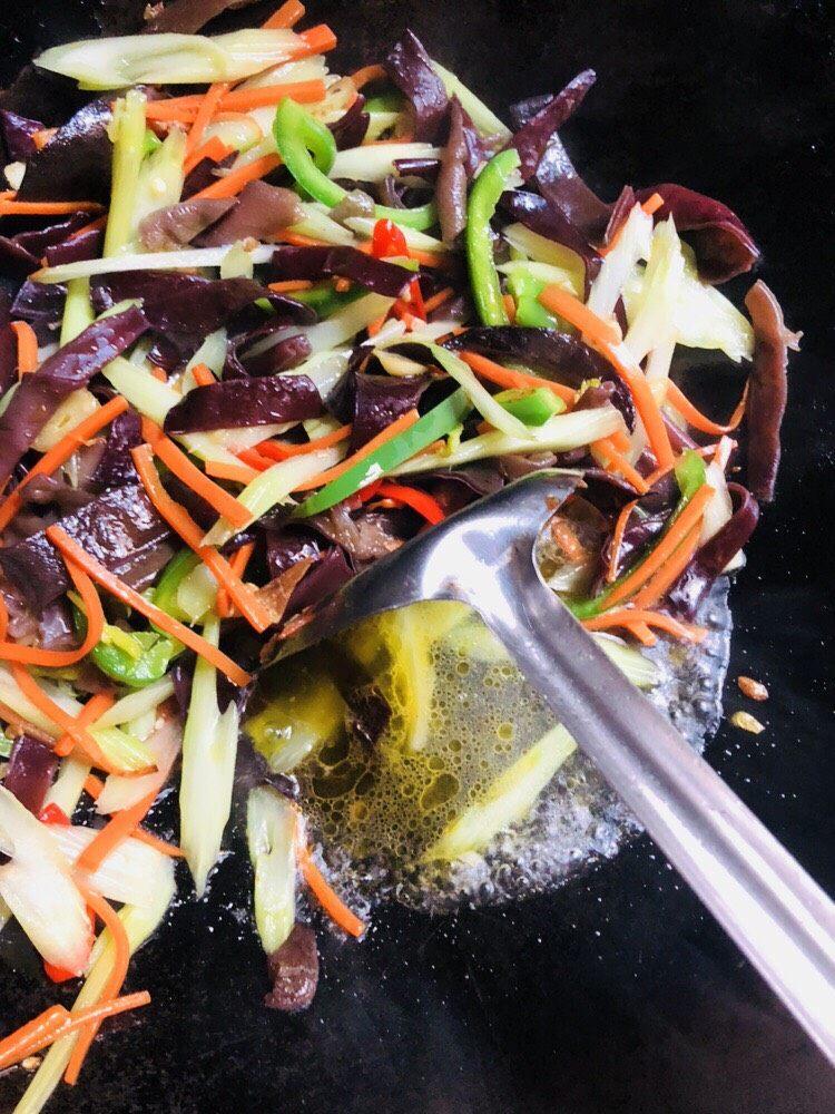 芹菜炒木耳,翻炒至青椒变色后加入适量清水,加入水能更好地融合各个菜的味道
