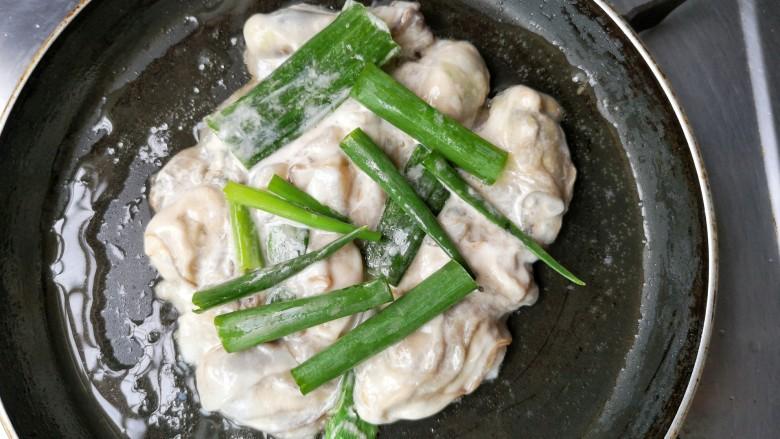 牡蛎炒蛋,摊平,煎一会,放入葱段。