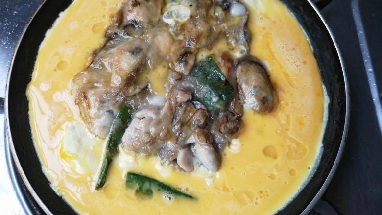 牡蛎炒蛋,翻一下煎另一面,在海蛎周围倒入蛋液。