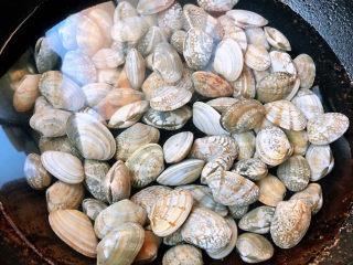 花蛤粉絲,鮮活的花蛤買回來在鹽水中浸泡半小時吐沙子再清洗干凈鍋中放入清水倒入花蛤大火煮起來