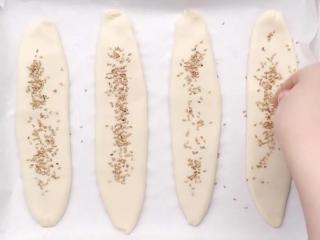 空心糖燒餅,將搟好的面片放在烤盤上,收口向下。在表面刷上一層水,撒上白芝麻。