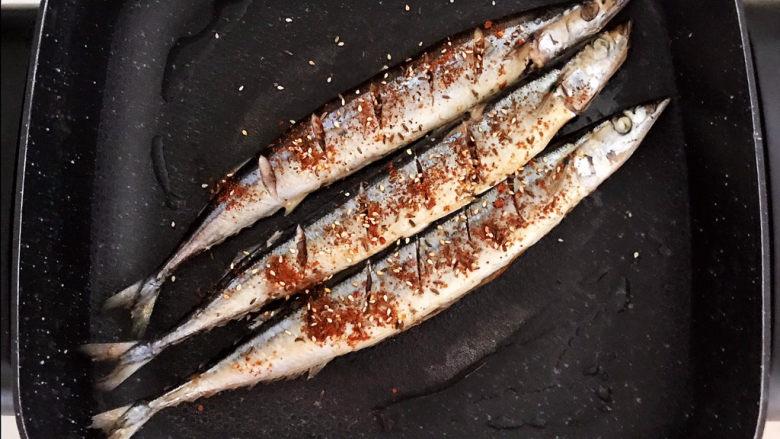 干煎秋刀鱼,煎至两面金黄后撒入干料,煎制5分钟
