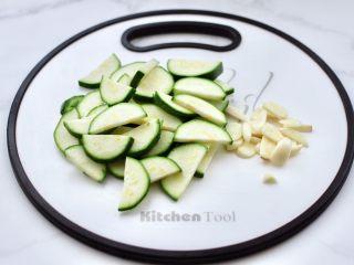 西葫蘆炒木耳,角瓜洗凈后用刀切成薄片,大蒜去皮切片。