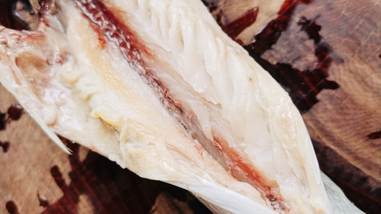 酱焖鲅鱼,用剪刀从<a style='color:red;display:inline-block;' href='/shicai/ 398'>鲅鱼</a>腹部向上剪开至鱼口,去除内脏,再把鱼腹内靠近主刺的瘀血去掉,用清水清洗干净。