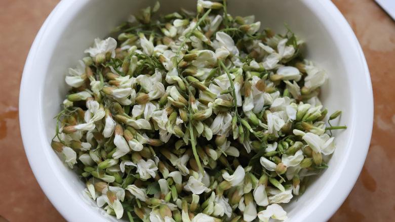 槐花麦饭,槐花捋干净,清水里加一点点盐,淘洗几遍,洗干净泥沙。