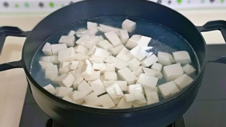 海带豆腐汤,锅中加入水烧开,下豆腐块焯水,大火煮1分钟捞出淋干水分。