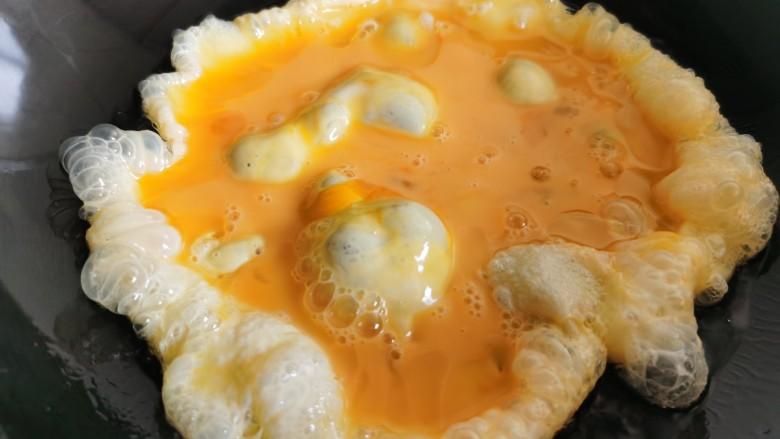 豇豆炒鸡蛋,炒锅烧热放油,倒入蛋液翻炒至蛋液凝固。