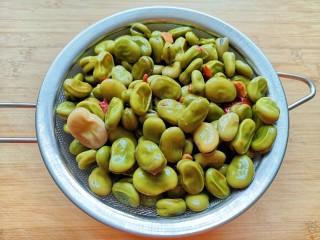 油炸蚕豆,煮好的蚕豆捞出,放在滤网里面沥干水分。
