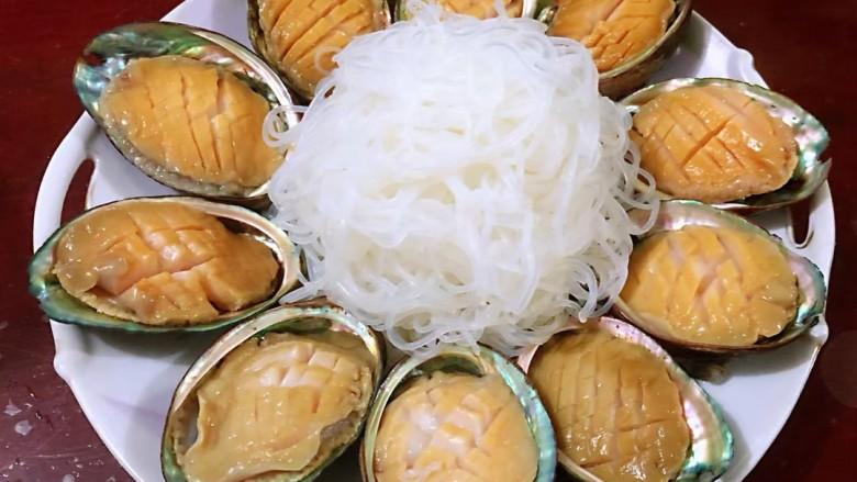 蒜蓉粉丝蒸鲍鱼,装壳摆放在盘中,把泡好的粉丝放入盘中央。