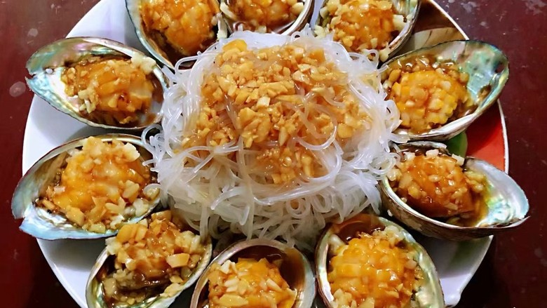蒜蓉粉丝蒸鲍鱼,把炝好的油蒜汁均匀倒在鲍鱼肉上,粉丝上。