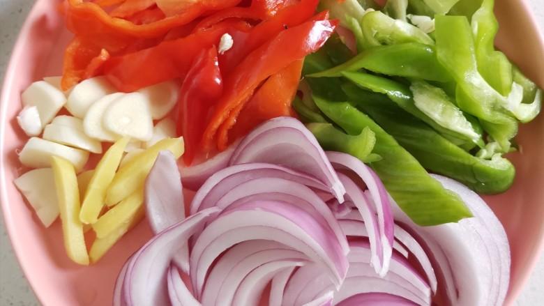 杏鲍菇炒牛肉,将洋葱,青红椒切丝,姜蒜切片备用