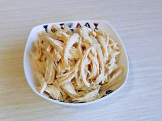 手撕鸡胸肉,煮熟的鸡胸肉用冷水冲洗,再手撕成条状。