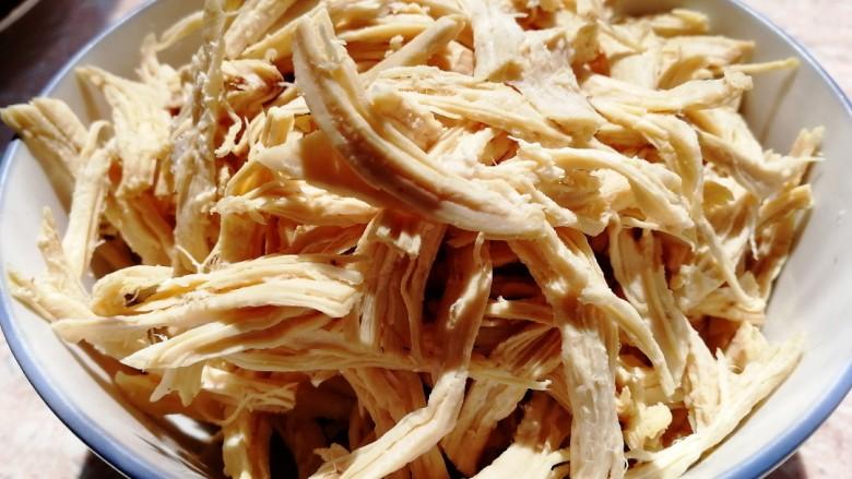 手撕鸡胸肉,鸡胸肉在汤汁中冷却,捞出手撕成条。