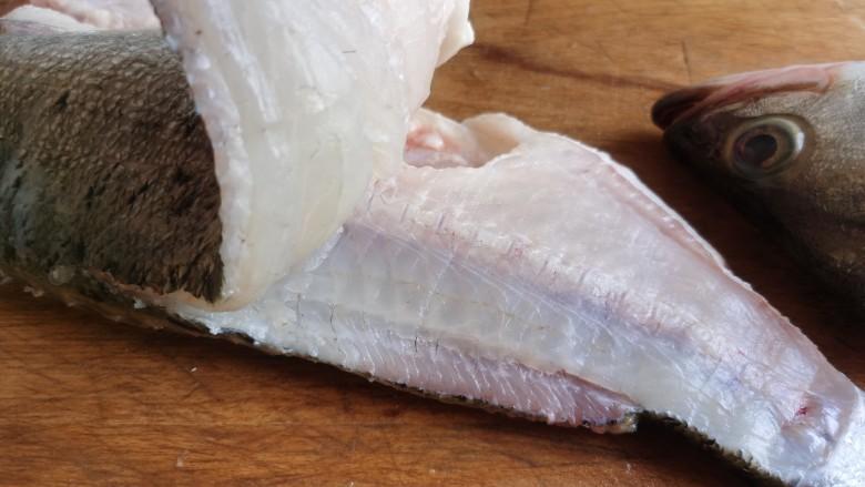 糖醋鲈鱼,用刀从鲈鱼的颈部开始,贴着鱼脊骨把鱼肉片到鱼尾处。同样的方法把另一面的鱼肉也片下来。