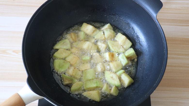 糖醋茄子, 将茄块倒入油锅中炸至表面定型后再翻动,使茄块受热均匀,炸至表面金黄后捞出;
