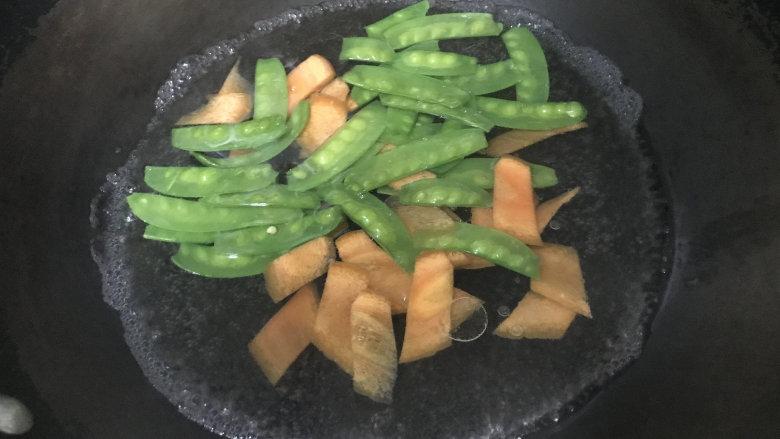 爆炒猪耳朵,炒锅烧沸水,淋少许油和食盐,放入荷兰豆和胡萝卜