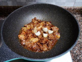 杏鮑菇燒雞塊,放入生姜和大蒜翻炒均勻。