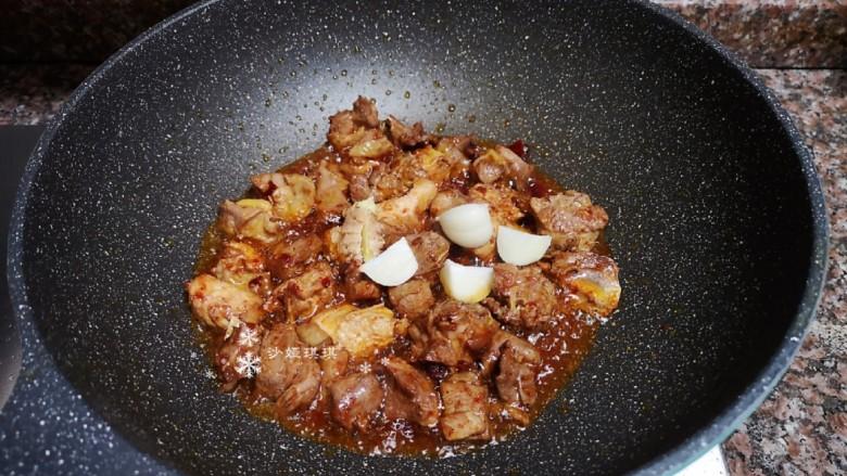 杏鲍菇烧鸡块,放入生姜和大蒜翻炒均匀。