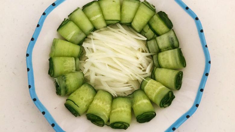 手撕鸡胸肉,把黄瓜卷围在盘边,圆葱丝放在盘底