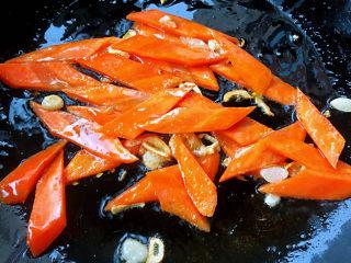 西兰花炒牛肉,锅中倒入底油加热放入蒜爆香再放入胡萝卜片炒匀