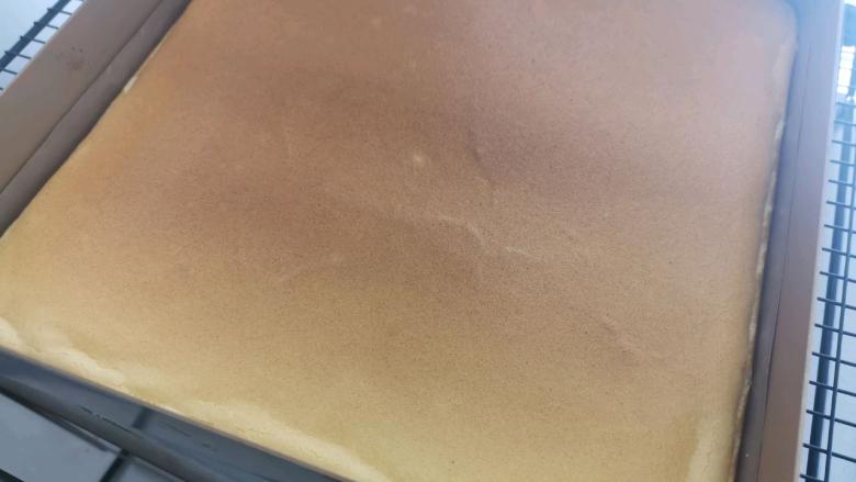 血橙蛋糕卷,取出烤好的蛋糕,轻震两下,移出烤盘放在晾网上,盖上油纸。