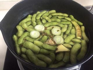 香辣毛豆,锅里放水、葱、姜、花椒把毛豆煮熟,水开煮五分钟左右就熟了。
