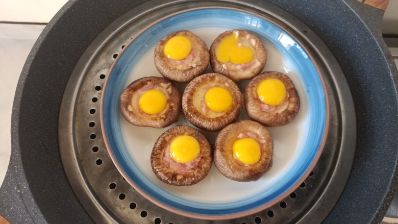 香菇鹌鹑蛋,放入一个笼屉,将盘子摆放在上面。