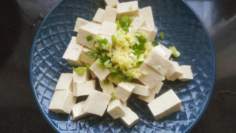 豆腐炒鸡蛋,把豆腐放入盘中。加入葱花姜末